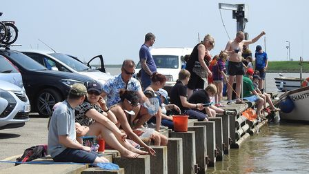Visitors at Orford Quay in Suffolk take up the challenge of catching as many crabs as possible durin