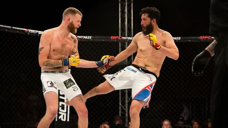 Sean Carter lands a leg kick in his main event with Tim Barnett at Cage Warriors 105 in Colchester.