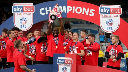 Lincoln City's John Akinde and the Lincoln City's players celebrate with the league two trophy after