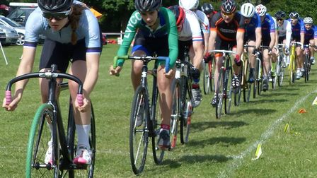 Matilda Guerney and Ellie-Mae Pledger lead a string at the West Suffolk Wheelers grass track event.
