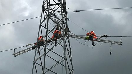 Workers from UK Power Networks install electrical equipment on overhead lines between Bramford and L