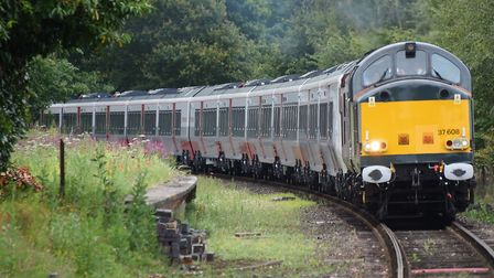 One of Greater Anglia's new trains arrives at the Mid Norfolk Railway, pulled by a diesel engine, to