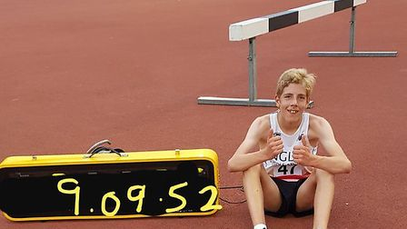 Ben Peck, pictured by the clock with his finishing time, the fastest 3,000m in the UK by an under-1