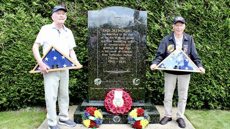 Bill Hennessey, left, and Dick Nelms with the flags presented to them after the re-dedication of the