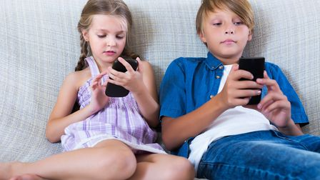 Children playing on mobile phones.