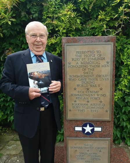 Clifford Hall in the Appleby Rose Garden standing next to the monument for the 94th Bombardment Grou