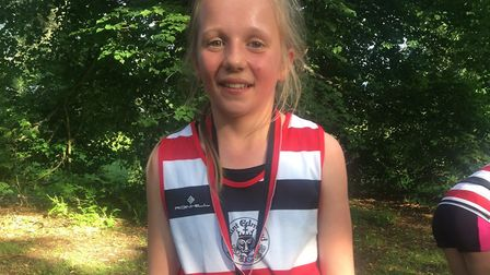 Verity Valentine, with her finisher's medal after finishing first girl in the junior race at the Bur