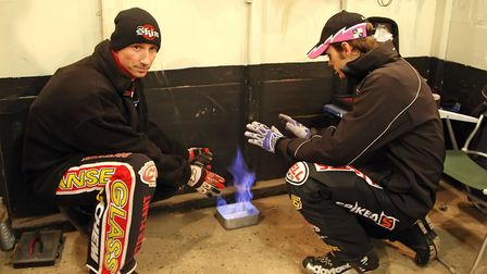 Shane Parker, left, and Roy Schlein find their own way to keep warm in the pits at the Kim Jansson b