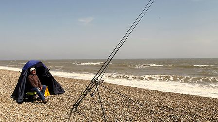 A fisherman waiting for his catch on Dunwich beach Picture: MICK WEBB