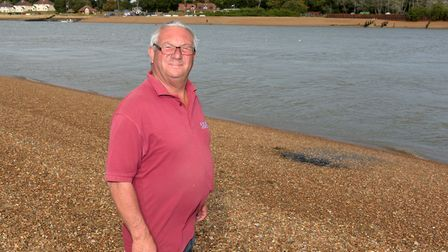 Stephen Read next to the black area on the beach that has been caused by a septic tank Picture: SAR