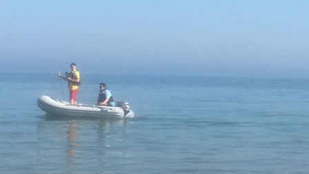 A couple of officials in a dinghy warn people to get out of the water at the sea in Frinton, Essex