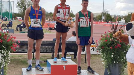 Lewis Sullivan, centre, on top of the podium after winning the under-15 boys' 1,500m titile at the E