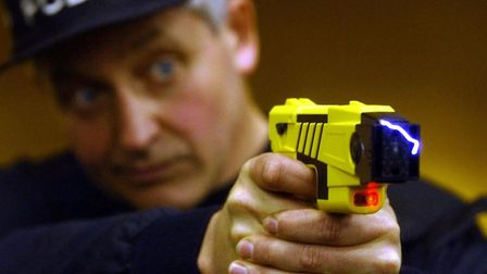 A policeman demonstrating a US-style taser stun gun Picture: PA WIRE