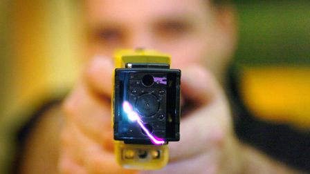Police officer demonstrating a Taser gun Picture: DANNY LAWSON/PA WIRE