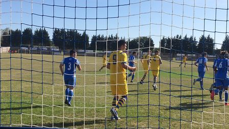 Sean Marks (yellow shirt) is in the Hullbridge Sports penalty area waiting for a delivery during a d