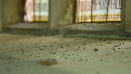 Bat droppings on the windowsill by one of the stained glass windows inside All Saints Church in Weth