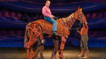 Michael Morpurgo sitting astride Joey, the sophisticated, life-sized puppet created for the National