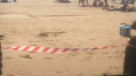 Warning tape on the beach in Frinton on Sea, Essex, after emergency services received several report