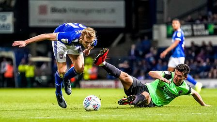 Flynn Downes struggles to stay upright after a challenge by Callum Reilly. Picture: STEVE WALLER