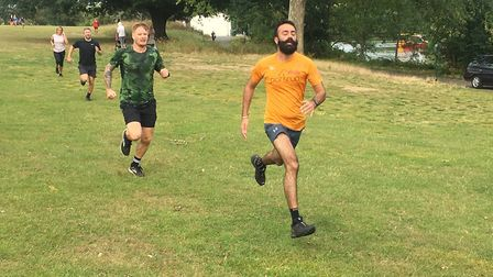 Runners sprint to the finish, with the lake in the background, during last Saturday's Harrow Lodge p