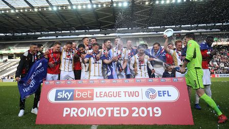 MK Dons players celebrate League Two promotion. Photo: PA