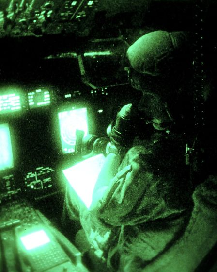 The pilot and cockpit of a C-130 Hercules transport aircraft through an image intensifying lens Pict