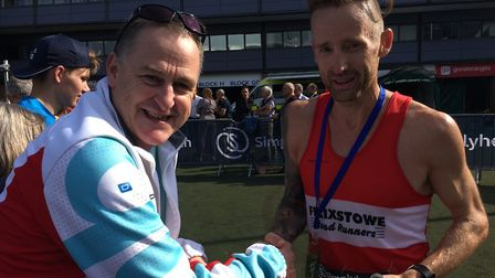 Danny Rock, right, shakes hands with his coach, Nigel Powley, after finishing third in a personal be