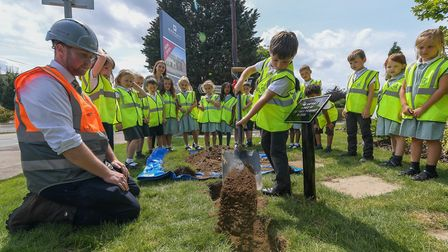 Site manager Ben Sharp and children from the The Pines Primary School bury the time capsule Picture: