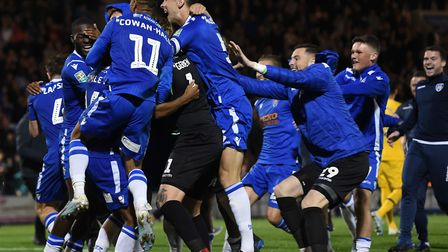 Colchester United players jump on Tom Lapslie after he scored the winning penalty in the Carabao Cup
