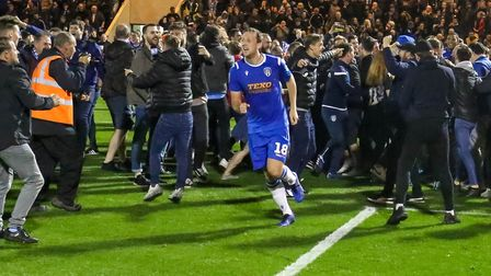 Colchester United stalwart Tom Eastman celebrates with fans on the pitch after the U's had knocked S