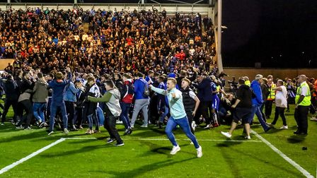 Fans flood onto the pitch after Colchester United's famous victory over Tottenham on penalties in th
