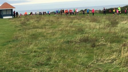 A procession of runners and walkers on the grassy section above the cliffs at the Hunstanton parkrun