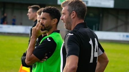 Woodbridge Town boss, Jamie Scales, gets ready to come on as a substitute while Carlos Edwards takes