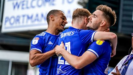 Luke Garbutt is congratulated by team-mates Flynn Downes and Kayden Jackson, after giving Town the l