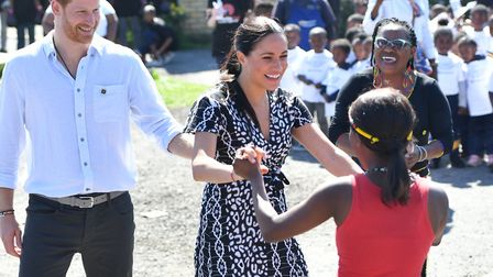 The Duchess of Sussex joins in with dancers as she and the Duke of Sussex leave the Nyanga Township
