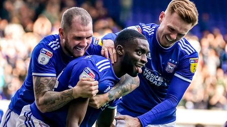 Kane Vincent-Young is hugged by teammates James Norwood and Jon Nolan after scoring Town's fourth in