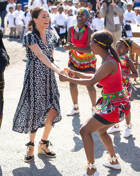 The Duchess of Sussex joins in with dancers as she leaves the Nyanga Township in Cape Town, South Af