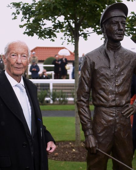 Lester Piggott with his bronze sculpture in the parade ring at the Rowley Mile Racecourse at Newmark