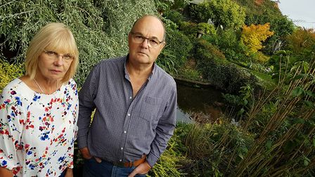 Robert and Elaine Peckham and their pond which has been affected badly by the sewage. PICTURE: RACHE
