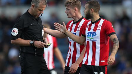 Lincoln City's Jorge Grant (right) and Callum Connolly have a chat with referee Christopher Sarginso