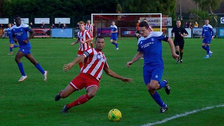 Bury Town's Ollie Hughes on the attack, taking on home defender Dan Davis during the 2-1 win at Feli