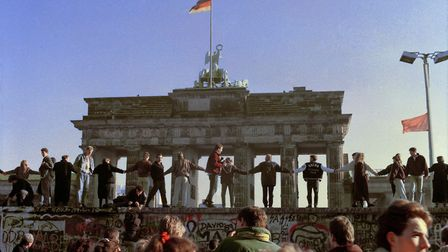 This November 10, 1989 file photo shows Berliners singing and dancing on top of the Berlin wall to c