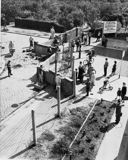 Berlin about to be divided. Residents of West Berlin, right, watch East German construction workers
