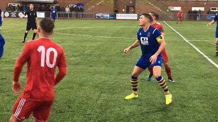 AFC Sudbury's Joe Whight (blue) in action during the FA Trophy second round tie at Worthing, in West