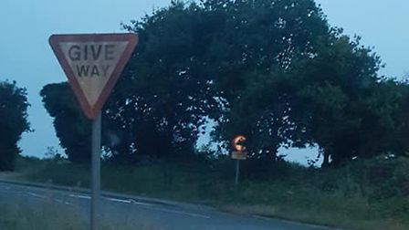 In the distance a small sign has been entirely obscured by the hedge meaning drivers won't be able t