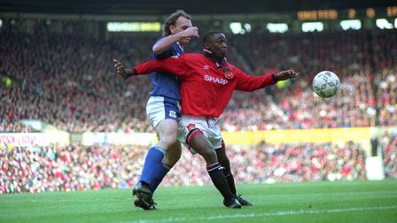 Manchester United's Andy Cole, right, shields the ball from Ipswich's John Wark during their Premier
