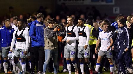 Colchester United players celebrate with their fans on the pitch after their Carabao Cup fourth roun