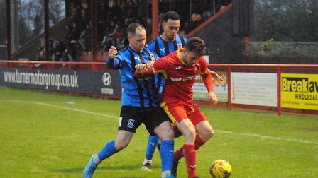 Callum Sturgess fends off the challenge of two Stourbridge players, during Saturday's 3-3 draw at Bl