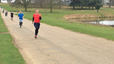 A procession of runners make their way to the finish of the Holkham parkrun, beside the lake, in Nor