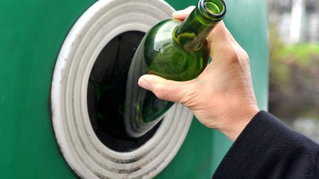 Glass bottle being put into a recycling bin Picture: GETTY IMAGES/ISTOCKPHOTO